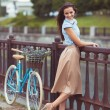 Young beautiful, elegantly dressed woman with bicycle — Stock Photo #61533687