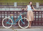 Young beautiful, elegantly dressed woman with bicycle — Photo