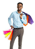 Happy african american man holding shopping bags on white backgr — Stock Photo