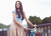 Young beautiful, elegantly dressed woman with bicycle in the par — Stock Photo