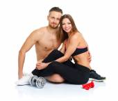Athletic couple - man and woman after fitness exercise sitting w — Stock Photo