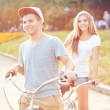 Young man and woman riding a bicycle in the park outdoors — Stock Photo #65009693