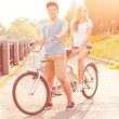 Young man and woman riding a bicycle in the park outdoors — Stock Photo #65009703