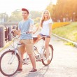 Happy couple riding a bicycle in the park outdoors — Stock Photo #65666631