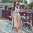 Young beautiful, elegantly dressed woman with bicycle — Stock Photo #70726071