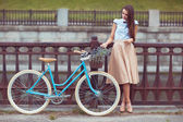 Young beautiful, elegantly dressed woman with bicycle — Stock Photo
