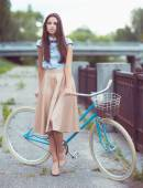Junge schöne, elegant gekleidete frau mit fahrrad — Stockfoto