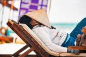 Vietnamese fruits saleswoman resting on a lounger on the beach — Stock Photo