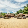 Wooden chairs and umbrellas on sand beach  — Stock Photo #69353377