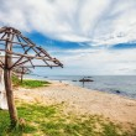 Wooden umbrellas on sand beach  — Stock Photo #69353399
