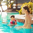 Child with mother by the pool — Stock Photo #79995548