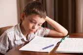 Sad boy doing homework — Foto Stock