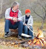Grandfather and grandson around a campfire  — Stock Photo