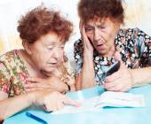 Two old women consider receipts — Stock Photo
