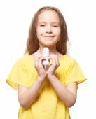 Girl holding an energy saving lamp — Stock Photo