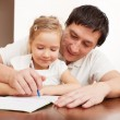 Father helping daughter doing homework — Stock Photo #66196639