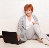 Woman sitting on floor with laptop — Stock Photo