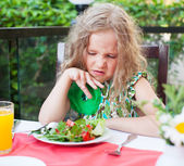 Child with disgust looking at salad — Stock Photo