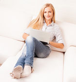 Woman on the sofa with laptop — Stock Photo