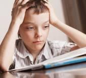 Sad boy doing homework — Stock Photo