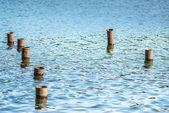 Metal poles in water — Stock Photo