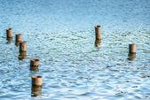 Metal poles in water — Stock Photo