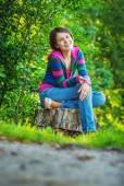 Girl sits on stub — Stock Photo