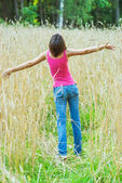 Young female stands in crop field — Stock Photo