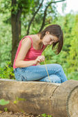 Girl outdoors in woods sitting on log — Stock Photo