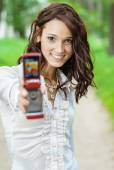 Girl stretches mobile phone — Stock Photo