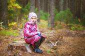 Little girl on stump — Stock Photo