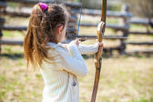 Little girl shoots bow — Stock Photo