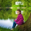 Little girl sits near lake — Stock Photo #53525183