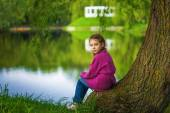 Little girl sits near lake — Foto Stock