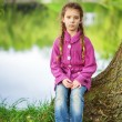 Little girl sits near lake — Stock Photo #54218063