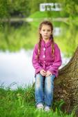 Little girl sits near lake — Foto de Stock