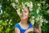 Smiling girl near blooming jasmine — Stock Photo