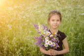 Little girl holding wildflowers — Stock Photo