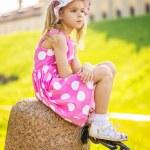 Little sad girl sits on rock — Stock Photo #55920567