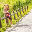 Little sad girl sitting on wooden fence — Stock Photo #55920865