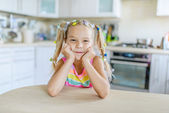 Little smiling girl sits at table — Foto Stock