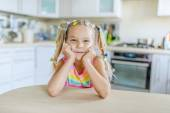 Little smiling girl sits at table — Stockfoto
