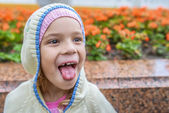 Little girl happy shows tongue — Stock Photo
