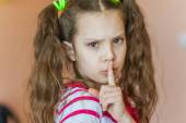 Little girl putting finger to his lips — Stock Photo