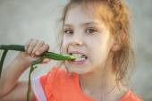Little girl eats green feather bow — Stock Photo