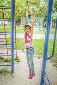 Little girl hanging on sporting rings — Stock Photo