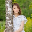 Portrait of young dark-haired woman embracing birch tree — Stock Photo #58003157
