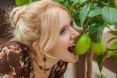 Woman bites green lemon — Stock Photo