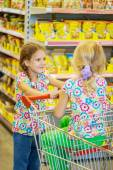 Little beautiful sisters in supermarket — Stock Photo