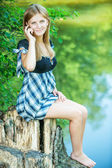 Portrait of young woman sitting on stump and speaking on mobile — Stock Photo